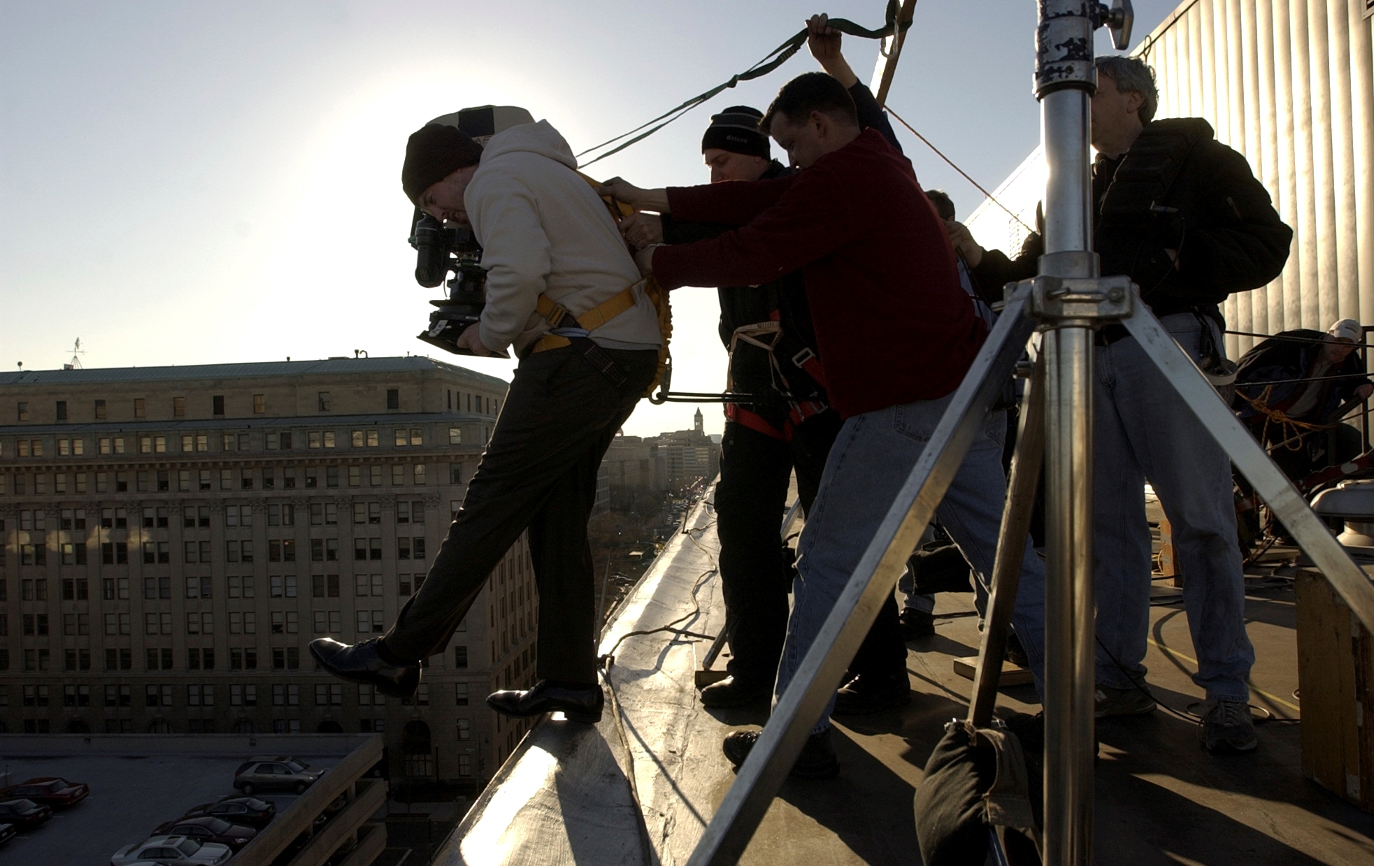"On the location for the filming of ""Thank You for Smoking"", Jason Reitman, director, held by James Whitaker, director of photography, center, and Ted Ayd, gaffer, films a scene from atop the Hyatt Regency, where Reitman films the street and his foot by leaning over the side with a camera."