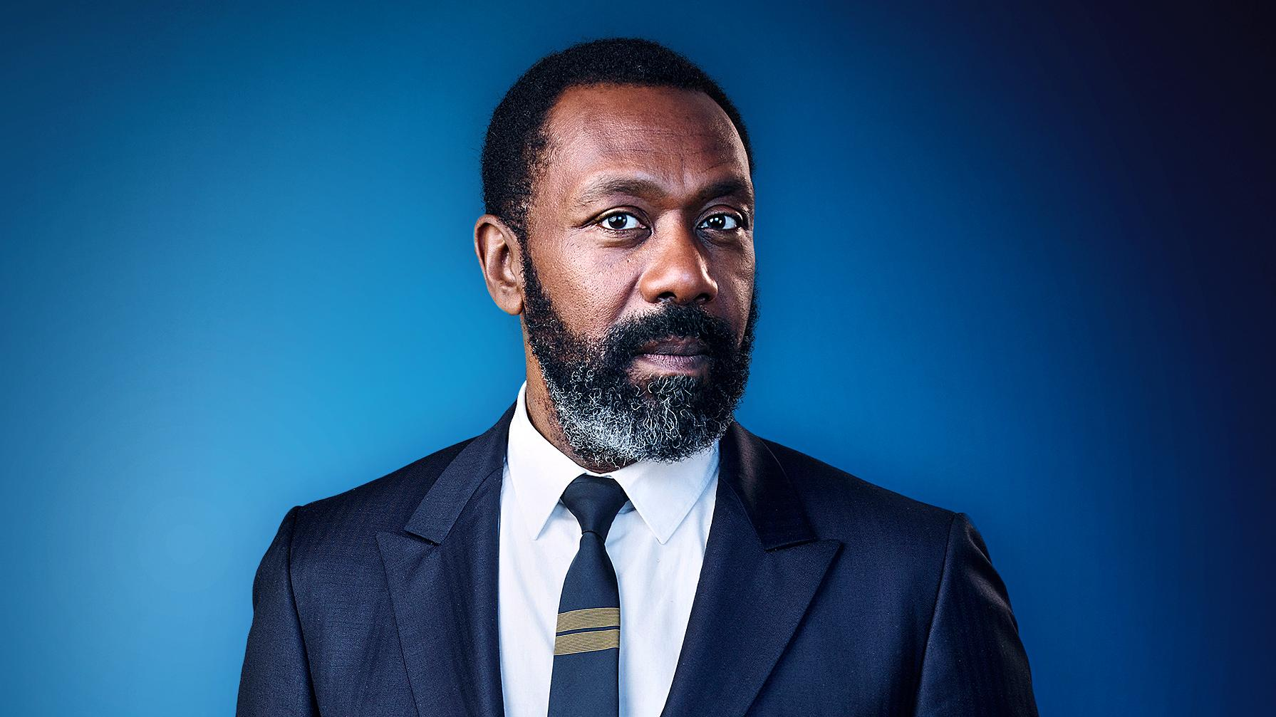 picture of lenny henry in a navy blue suit and blue background