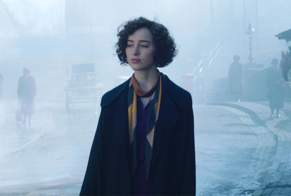 first look image of Phoebe Dynevor (Bridgerton) as Clarice Cliff in upcoming Sky Original film, The Colour Room, wearing priod clothing with a foggy city background